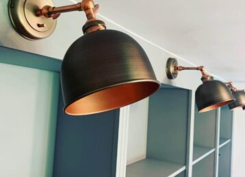 Close up of four metal dome wall lights getting further away placed above shelving