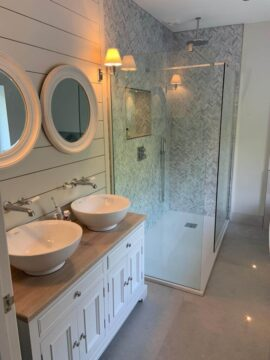 Bathroom with two mirrors and sinks and walk in shower surrounded by glass