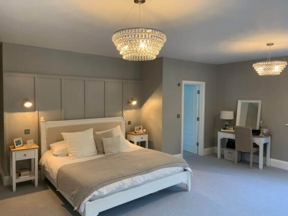 Bedroom with double bed in centre with two bed side tables. Small dressing table with mirror on right of open door and two large hanging lights