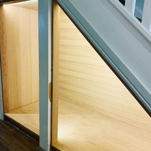 Under stairs area with wooden boarding shwoing light from recessed LED