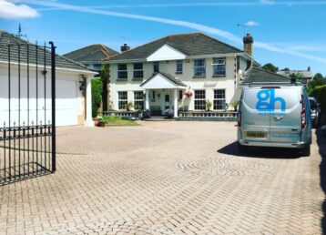 Looking through open gates to a gh electrical van parked on the right handside in a large driveway with a double garage on the left and onto a large house