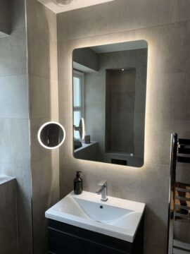 Fully tiled bathroom with mirror, towel radiator, floating sink with lights on mirror