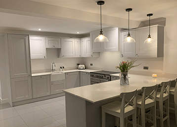 Kitchen with spot lights and 3 hanging black lights over worktop
